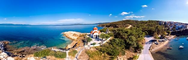 Church and sea with beach and mountains in nea roda, halkidiki, greece
