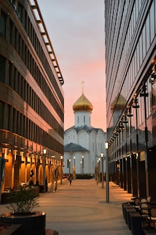 Church of st. nicholas the wonderworker among glass office buildings, church between glass office buildings at sunset