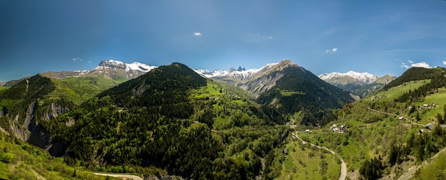 Church in a village in the french alps with mountains 3000 meters high. green meadows in spring. drone panning