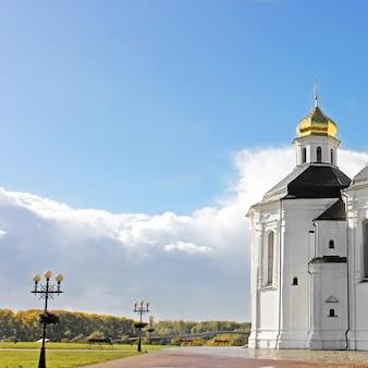 秋の公園にある黄金のドームのある教会
