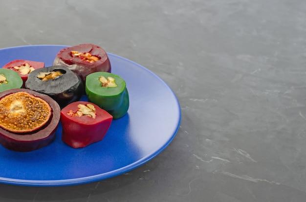 Чурчхела фруктовая пастилка с грецкими орехами, фундуком и инжиром, красиво нарезанная на синюю тарелку на темном столе с копией пространства.