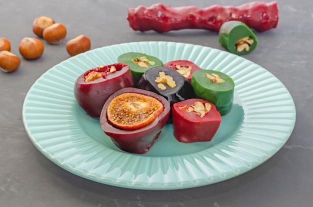Чурчхела с фруктовой пастилкой с грецкими орехами, фундуком и инжиром, красиво нарезанная на светло-синюю тарелку на темном столе.