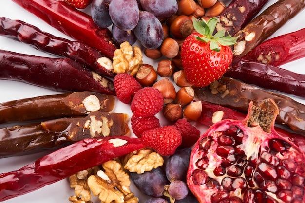 Смесь чурчхелы, фрукты, ягоды и орехи на белом столе, пищевой фон, кавказские сладости