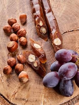 チャーチヘラ、ブドウジュースとヘーゼルナッツから作られたグルジアの国民的デザート、木製のテーブルで構成