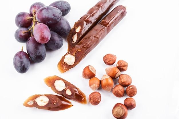 チャーチヘラ、ブドウジュースとヘーゼルナッツから作られた国のグルジアのデザート、白い背景の上の孤立した組成物、コピースペース