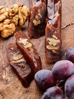 Чурчхела, национальный грузинский десерт из виноградного сока и грецких орехов, композиция на деревянном столе