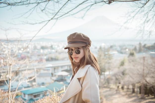 Турист красивой женщины усмехаясь на пагоде chureito и горе fuji, японии