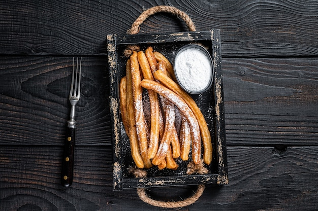 Churros fried sticks with sugar powder in wooden tray. black