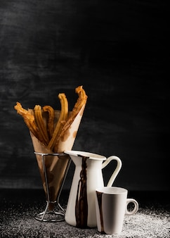 Churros in a glass and black copy space background