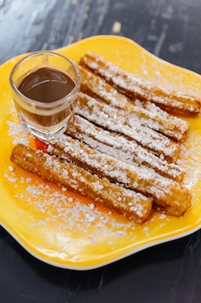 Churros topping with icing sugar served with nutella sauce on yellow plate.