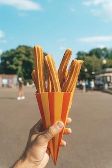 길거리에서 손에 쥔 츄러스 와플 반죽과 설탕 패스트푸로 만든 츄러스 길거리 음식 디저트...