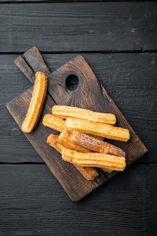 Churros with sugar, and chocolate sauce, on black wooden table background, top view flat lay