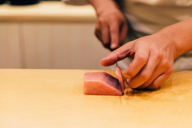 日本のおまかせシェフは、寿司を作るために木製のキッチンカウンターでナイフできれいに中脂肪クロマグロ(日本語でchutoro)をカットしました。日本の贅沢な食事。