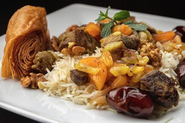 Чигиртма плов с мясом ягненка, сухофруктами, финиками и грецкими орехами, на белой тарелке