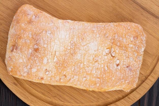 어두운 나무 테이블에 있는 커팅 보드에 있는 치아바타 빵, 공간이 있는 위쪽 전망.