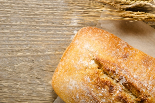 Ciabatta bread on a wooden table on baking paper. rustic style, italian.