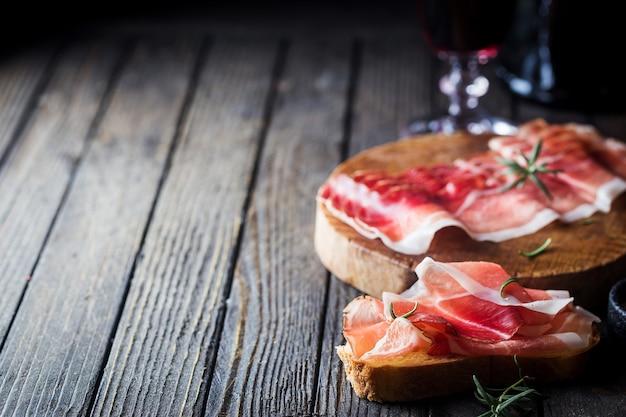Открытый бутерброд чиабатта с ветчиной ветчины на темном деревянном фоне. приготовление сэндвичей.
