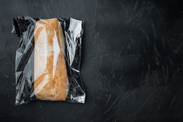 Ciabatta panini bread in a plastic bag, on black background, top view flat lay , with copyspace  and space for text