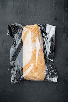 Ciabatta in a plastic bag, on black background, top view flat lay