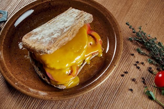 チャバタサンドイッチ、ファラフェル、ソース、モッツァレラチーズ、トマト、木製の表面にセラミックプレート。美味しくてヘルシーなストリートフードスナック