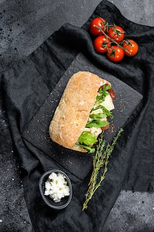 Ciabatta sandwich with fresh goat cheese, pear marmalade and arugula. black background. top view