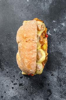 チャバタサンドイッチ、ミートボール、チーズ、トマトソース。黒の背景