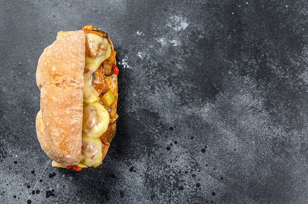Ciabatta sandwich with meatballs, cheese and tomato sauce. black background. top view. copy space