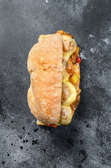 Ciabatta sandwich with meatballs, cheese and tomato sauce. black background