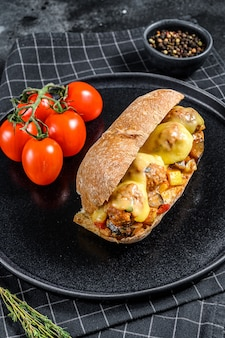 Ciabatta sandwich with meatballs, cheese and tomato sauce. black surface. top view