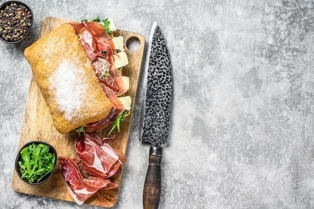 Сэндвич чиабатта с ветчиной прошутто-крудо, рукколой и сыром бри камамбер. серый стол. вид сверху. скопируйте пространство.