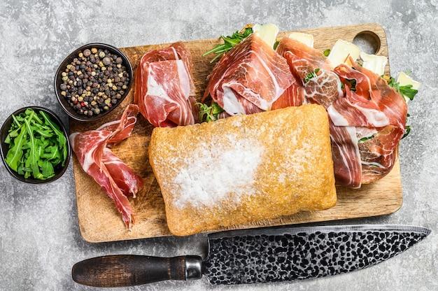 Сэндвич чиабатта с ветчиной прошутто-крудо, рукколой и сыром бри камамбер. серый стол. вид сверху.