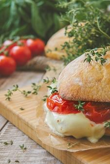 チャバタサンドイッチ、トマト、ハーブ、オイル、トーストしたガーリックチーズのパン。トーン。
