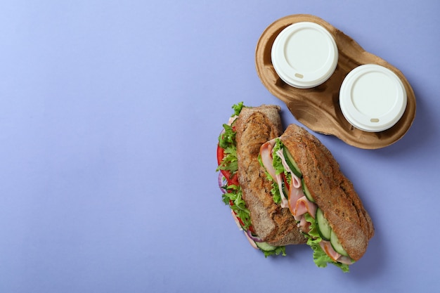 Ciabatta sandwiches and coffee cups on violet background