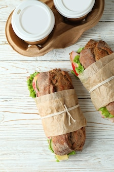 Ciabatta sandwiches and coffee cups on white wooden table
