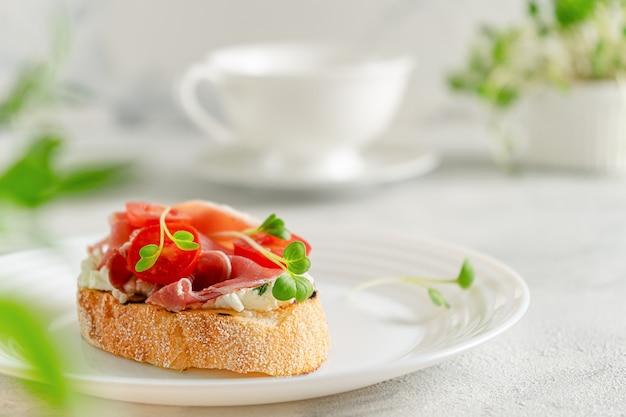 Тост чиабатта с прошутто или хамоном, помидорами и мягким сыром. средиземноморский завтрак. копировать пространство