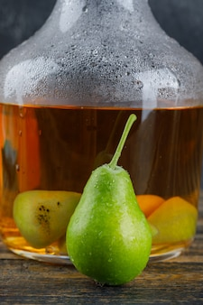 Cider drink with pear in a bottle on wooden table