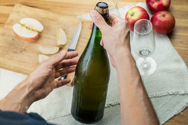 Взгляд сверху мужских рук держа закупоренную бутылку наградного cidre. снято сверху с красивой ледяной бутылкой яблочного вина в руках человека