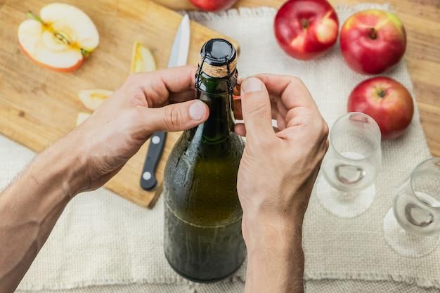 Взгляд сверху мужских рук раскрывая бутылку наградного cidre. снимок сверху откупорившей красивой ледяной бутылки яблочного вина