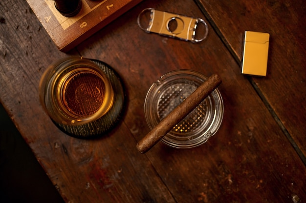 Cigar in ashtray and alcohol beverage in glass, lighter and guillotine on wooden table, top view, nobody