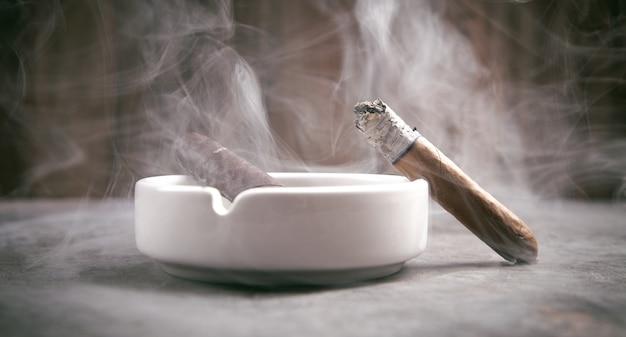 Cigar and ashtray on table. smoking