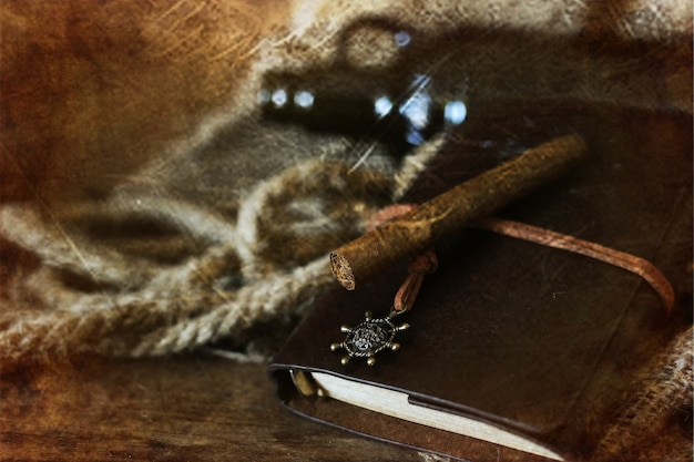 Cigar and leather on a wooden background with retro scratched effect on photo