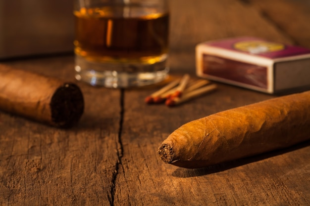 Cigar  on old wooden table with the best whisky