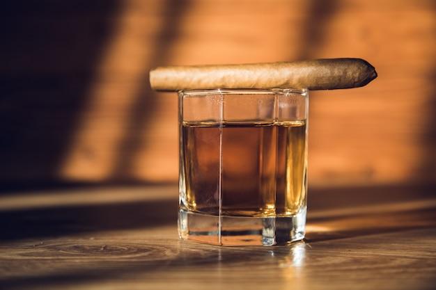 テーブルの上のウイスキーのグラスに葉巻