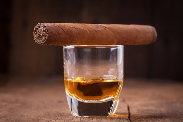 Cigar and whisky on old wooden table
