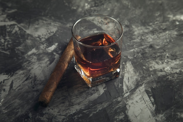 Cigar with glass of whisky on table