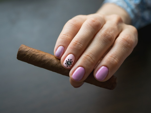 Cigar in woman hand, photo on gray table. creative manicure with painted virus on the nails, soft focus, close up.