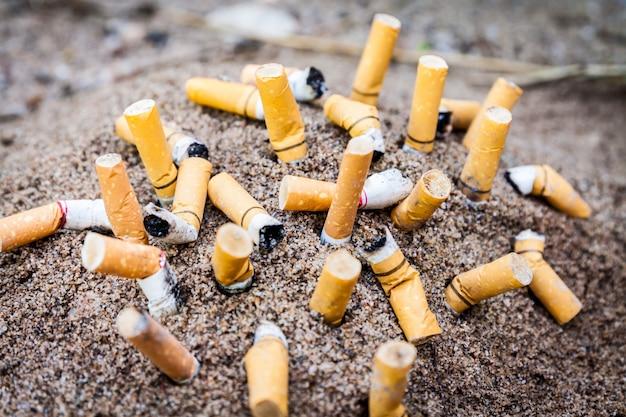 Cigarette in ashtray on sand
