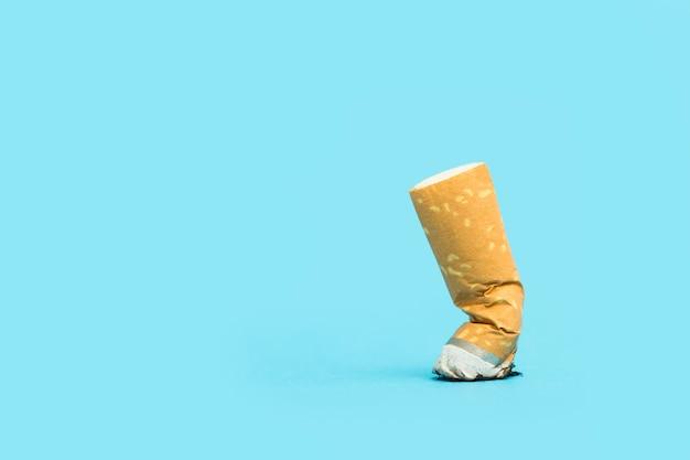 A cigarette butt on a light blue background