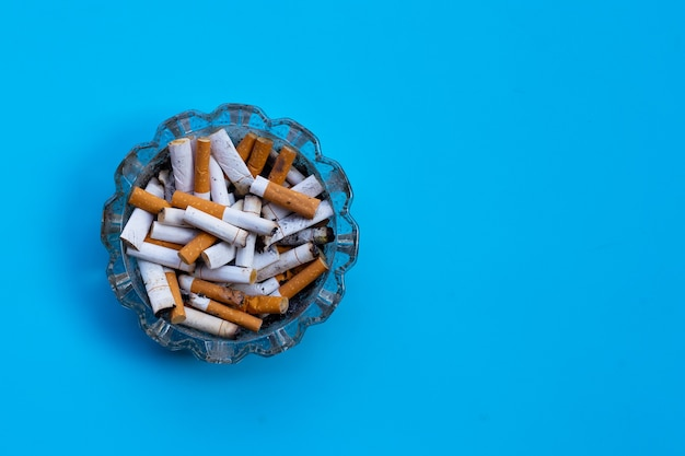 Cigarette butts in glass ashtray on blue surface