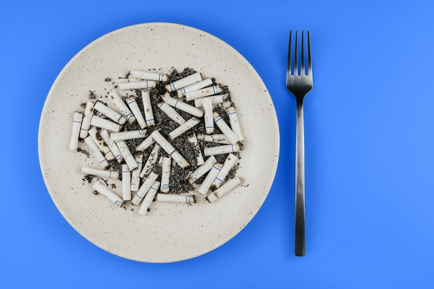 Cigarette butts on a plate and fork on a blue background copy space. cigarettes for lunch.